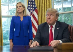 President Donald Trump, right, listens as Homeland Security Secretary Kirstjen Nielsen, left, addresses members of the media before Trump signs an executive order to end family separations at the border, during an event in the Oval Office of the White House in Washington, Wednesday, June 20, 2018. (AP Photo/Pablo Martinez Monsivais)