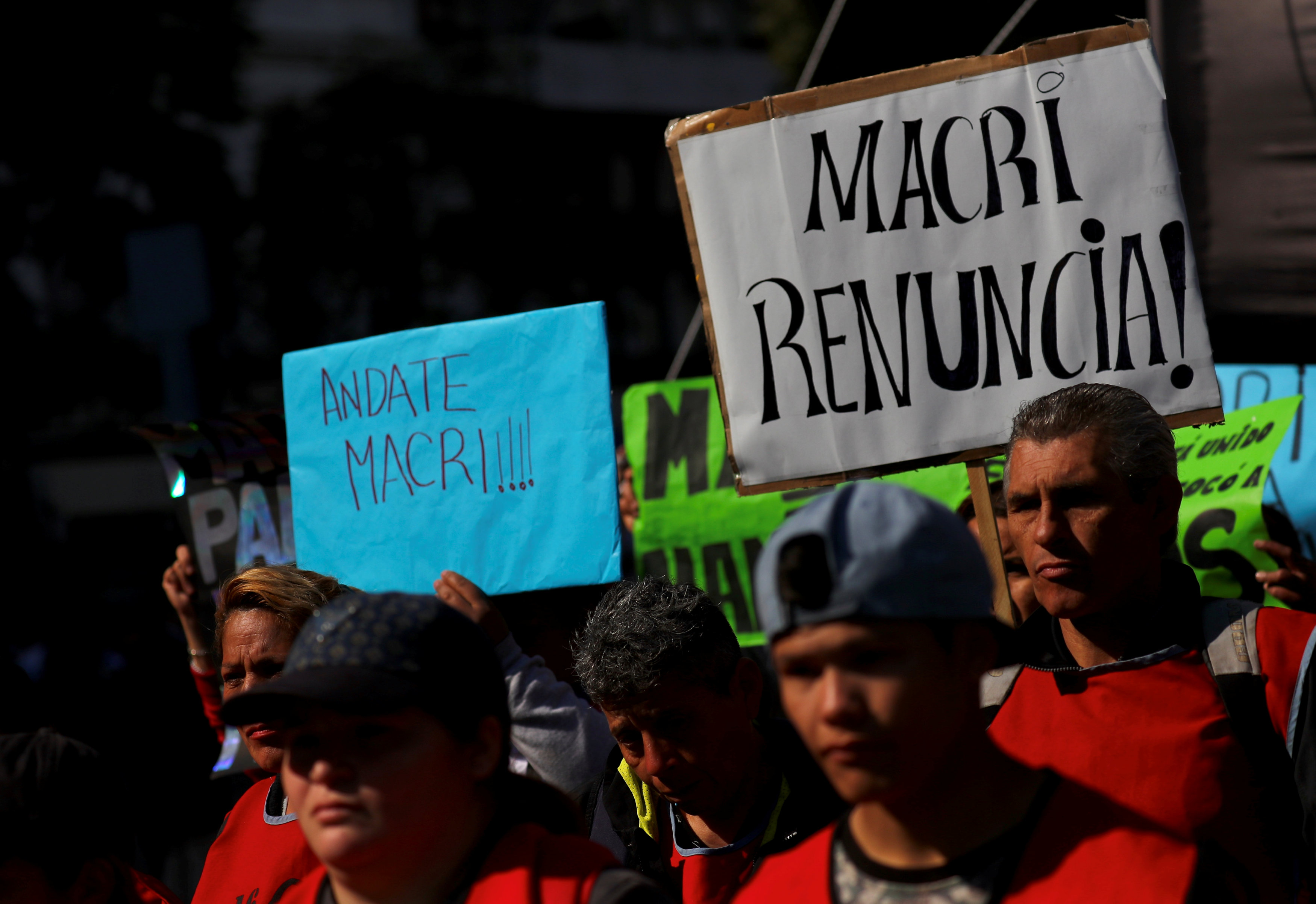 Demonstrators hold up signs during a protest against the government's economic measures in Buenos Aires
